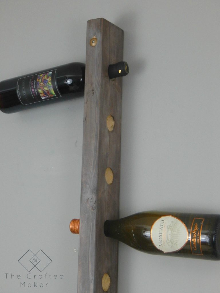 Build this DIY hanging wine rack out of one 2X4 board. For less than a bottle of wine, you can display your wine selection in style.